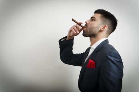 cigare: Businessman in a suit with red handkerchief smoking cigare