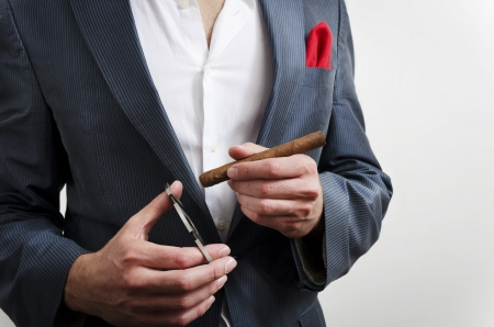 Businessman in a suit with red handkerchief smoking cigare photo