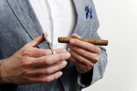 cigare: Businessman in a suit with blue handkerchief cutting cigare