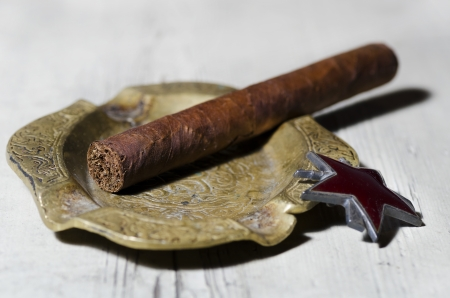 Handmade luxury Cuban cigar resting on an ashtray photo