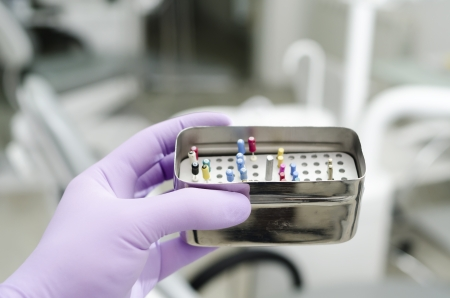 Gloved hand holding  endodontic boxes with probes