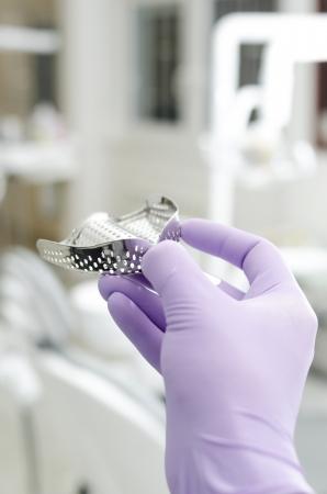 Gloved hand holding impression tray for prosthodontics photo