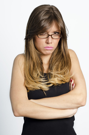 pouty: Pouting Teenage Girl. Teenage girl standing with her arms crossed looking frustrated, stubborn or pouty. Stock Photo