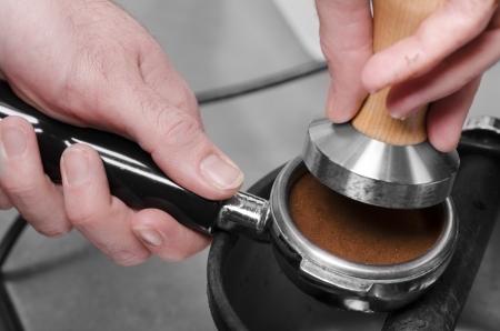 Barista with tamper and pistonportafilter making espresso. Stock Photo