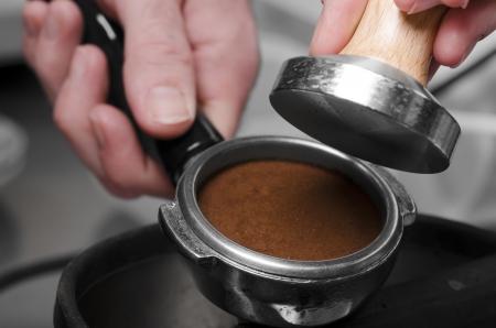 making coffee: Barista with tamper and pistonportafilter making espresso. Stock Photo