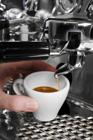 with coffee maker: Barista prepares espresso in his coffeeshop; close-up Stock Photo