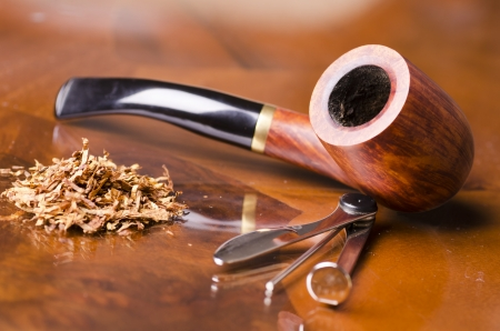 Smoking pipe and tobacco on wooden table