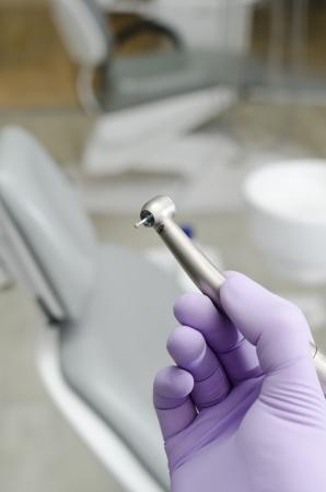 Hand of dentist holding dental drill machine with turbine Stock Photo
