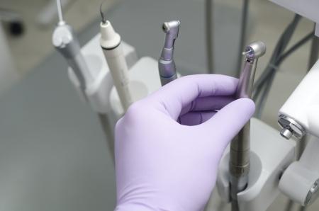 dental hygiene: Hand of dentist holding dental drill machine with turbine