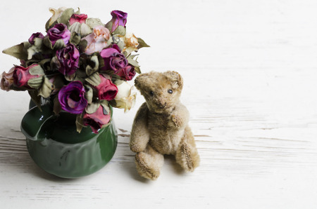 Old worn out teddy bear on wooden table photo