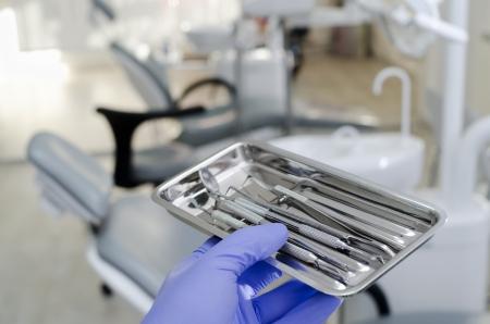 Gloved hand holding dental instruments in dental office