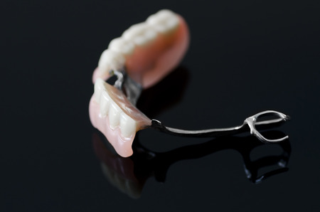 New dental prosthesis on black background photo