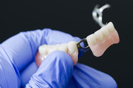 Gloved dentist hand, holding dental prosthesis on black background