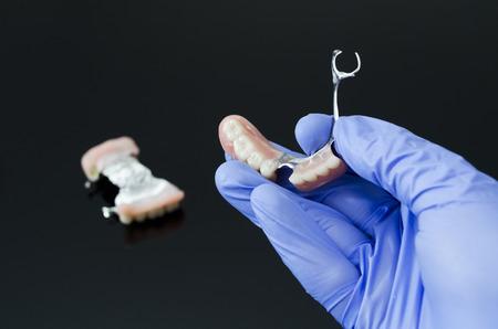 Gloved dentist hand, holding dental prosthesis on black background photo
