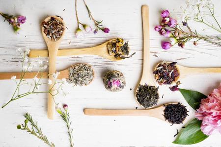 flores secas: Diferentes tipos de t� en cucharas de madera