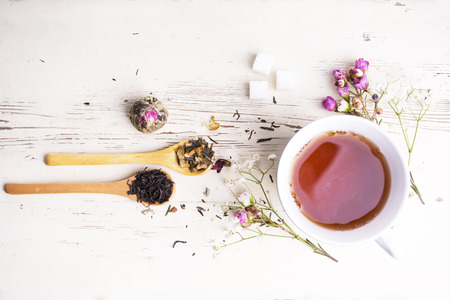 A cup of tea with flowers and tea around it Stok Fotoğraf