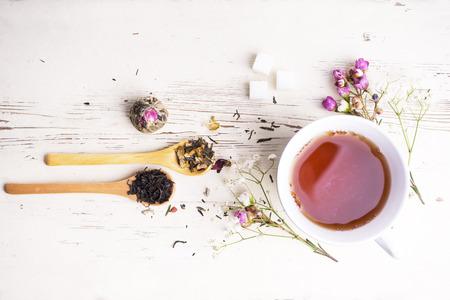 Une tasse de thé avec des fleurs et du thé autour d'elle