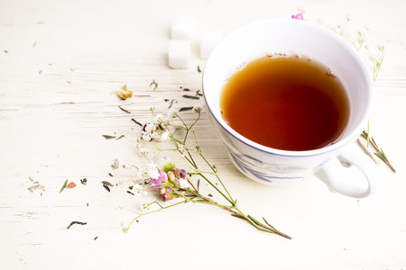 A cup of tea with flowers and tea around it Banco de Imagens