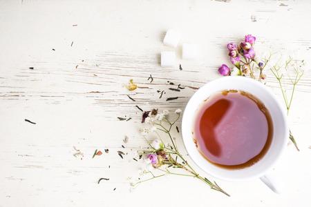 Een kopje thee met bloemen en thee eromheen