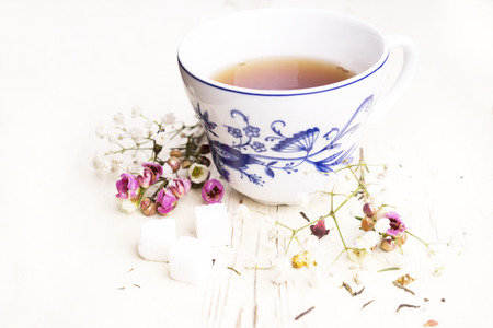 english tea: A cup of tea with flowers and tea around it Stock Photo