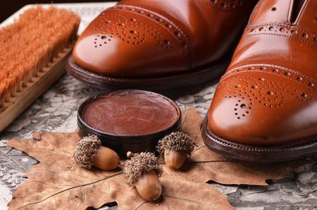 Sapatos de couro marrom na mesa com equipamentos de polimento