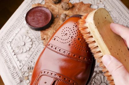 Sapatos de couro marrom na tabela com equipamentos de polimento