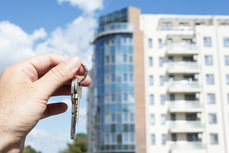 Hand holding keys in front of new building photo