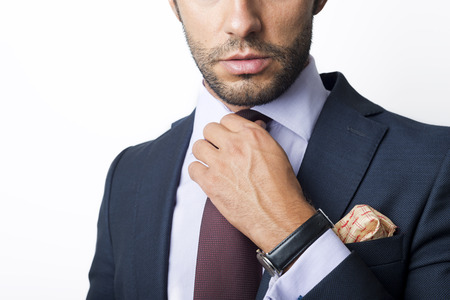 formal clothing: Mans style. dressing suit, shirt and cuffs. Fixing his tie. Stock Photo