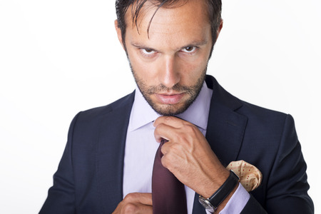 Mans style. dressing suit, shirt and cuffs. Fixing his tie. Stock Photo