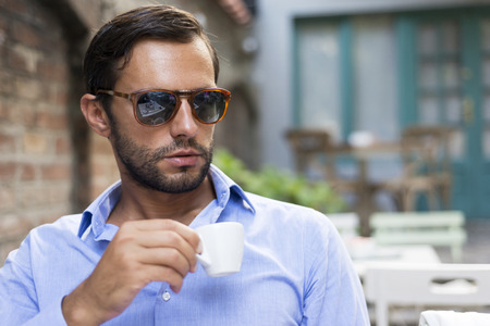 Young fashion man with beard drinking espresso coffee in the city cafe