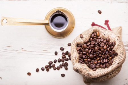The sack of coffee beans on wooden table photo