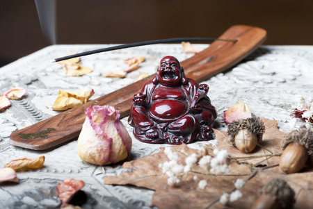 Buddah with scent stick on wooden table photo
