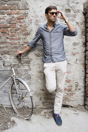 shoes: Casual young man stands with his back against a brick wall