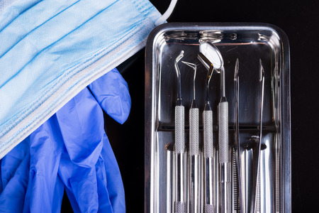Dental instruments with mask and extracted tooth on black
