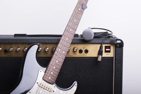 Black electric guitar, amp and mic on white background Foto de archivo