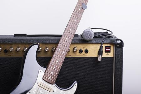 Zwarte elektrische gitaar, versterker en microfoon op een witte achtergrond Stockfoto