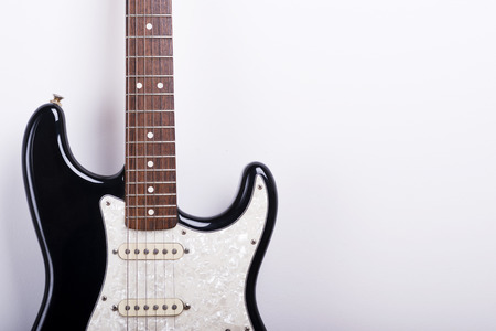 guitar tuner: Black electric guitar on white background
