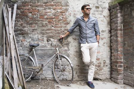 レンガの壁に背中とカジュアルな若い男が立っています。 写真素材