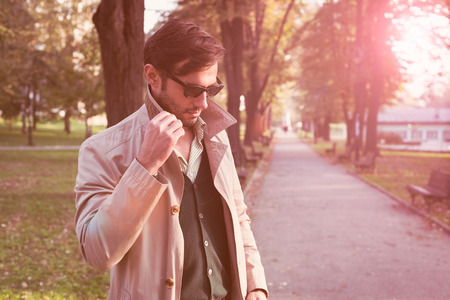 trench: Handsome man wearing trench coat in park