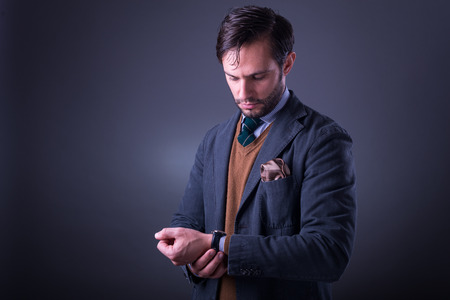Handsome man in suit with tie and pocket square, looking at his watch Stock Photo