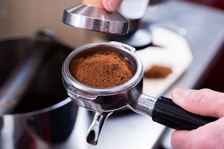Barista with tamper and pistonportafilter making espresso. Banco de Imagens