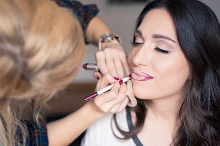 Young beautiful girl applying make up by makeup artist photo