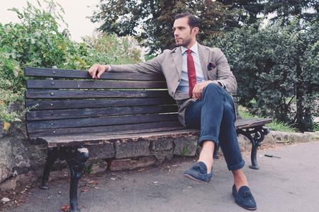 estilo urbano: Hombre de negocios joven hermoso en el parque despu�s del trabajo, estilo vintage, retro filtrada vistazo