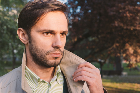 trench coat: andsome man wearing trench coat in park, retro vintage style filtered onH Stock Photo