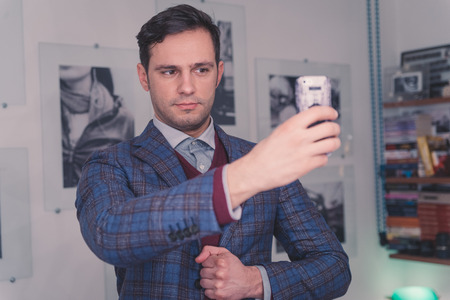 Handsome man in suit taking a selfie with his mobile phone photo