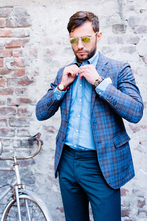 Handsome man with glasses ina suit, against old vintage wall, outdoors.