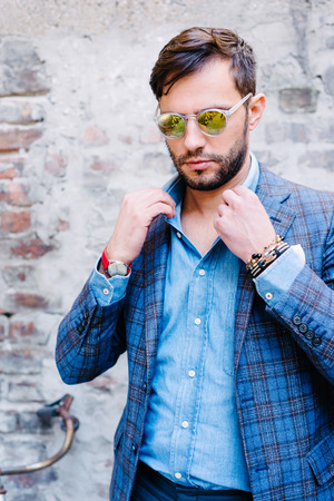 estilo urbano: Hombre guapo con traje vasos ina, contra la pared de �poca antigua, al aire libre. Foto de archivo