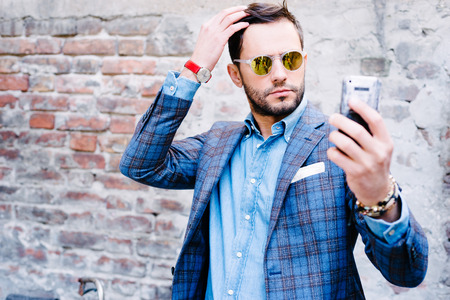 are taking: Handsome man with glasses ina suit, against old vintage wall, outdoors. taking a selfie