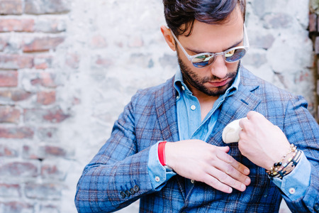 hand in pocket: Handsome man with glasses in a suit, against old vintage wall, fixing his pocket square