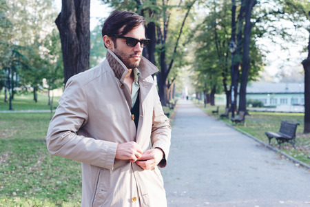 trench coat: Handsome man wearing trench coat in park